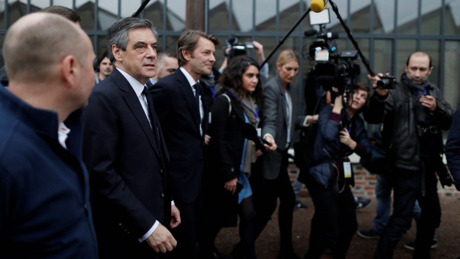 François Fillon (2nd L), a former French prime minister, a member of The Republicans political party and 2017 presidential candidate of the French center-right, and Troyes Mayor Francois Baroin visit Le Coq Sportif factory as they attend a campaign visit