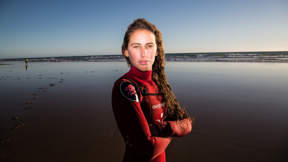 Moroccan surfer Meryem El Gardoum standing on a beach, looks directly at the camera.