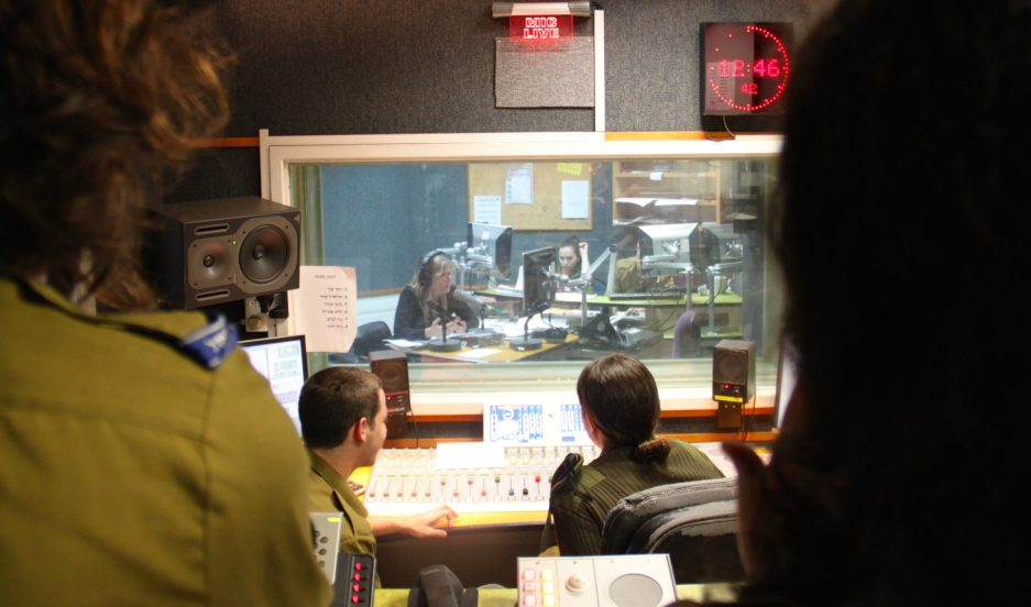 Soldiers in the production booth during a talk show at Galey Tzahal, Israel Army Radio's news talk channel.
