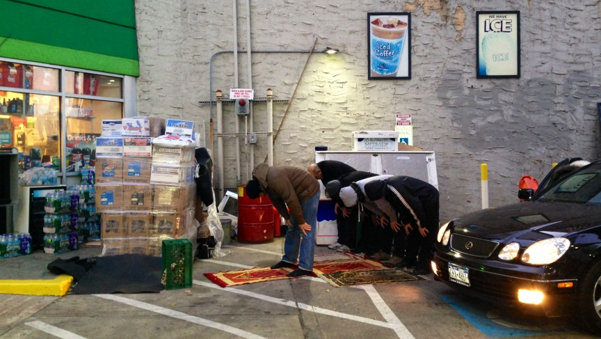Muslim cabbies pray at a BP station in downtown Manhattan while patrons pump gas.