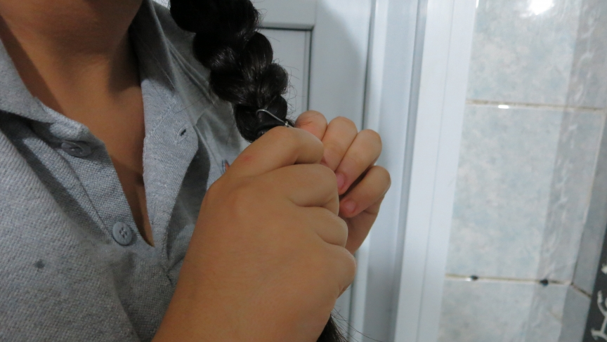 Fatma braids her hair before heading off on the two-hour ride to school. Her father's angry that school is 20 miles away and that Fatma must ride the public bus.
