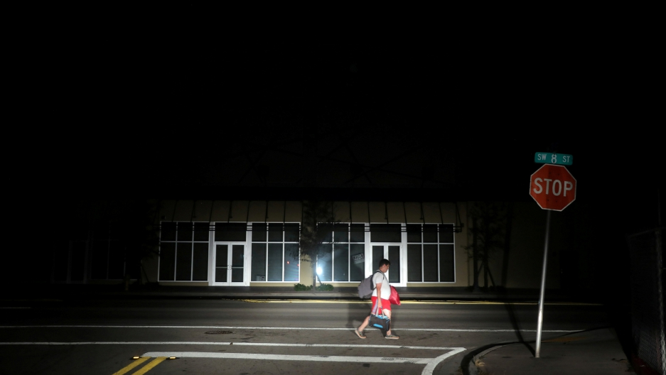 A man walks back home in the darkness as many areas of Miami still without electricity after Hurricane Irma plowed through the region.