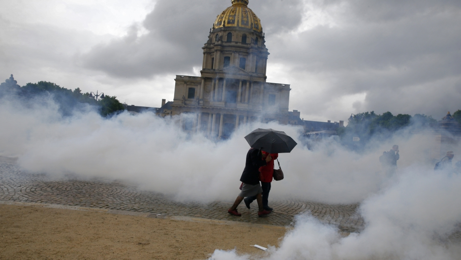 Clouds of tear gas surround people near the Invalides monument during clashes between protesters and French police during a demonstration against French labor law reform in Paris. May 12, 2016.