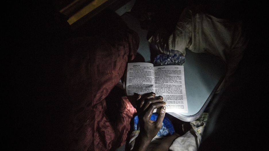 On a train home from Lagos to Kano, a Hausa woman reads a romance novel with the flashlight of her phone.