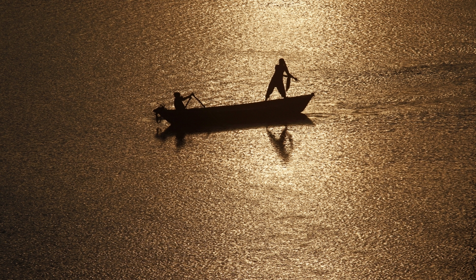 Fisherman are silhouetted against the rising sun in the waters of the Ganges river.