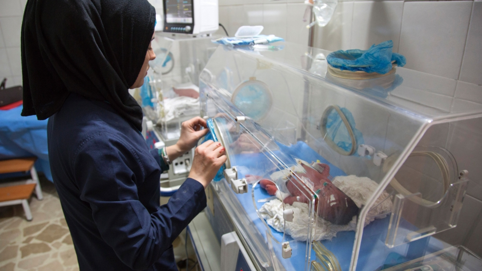 A Syrian nurse stands next to incubators with newborns who were evacuated by medical staff at a children's hospital into the basement following reported government bombardment on June 9, 2016.