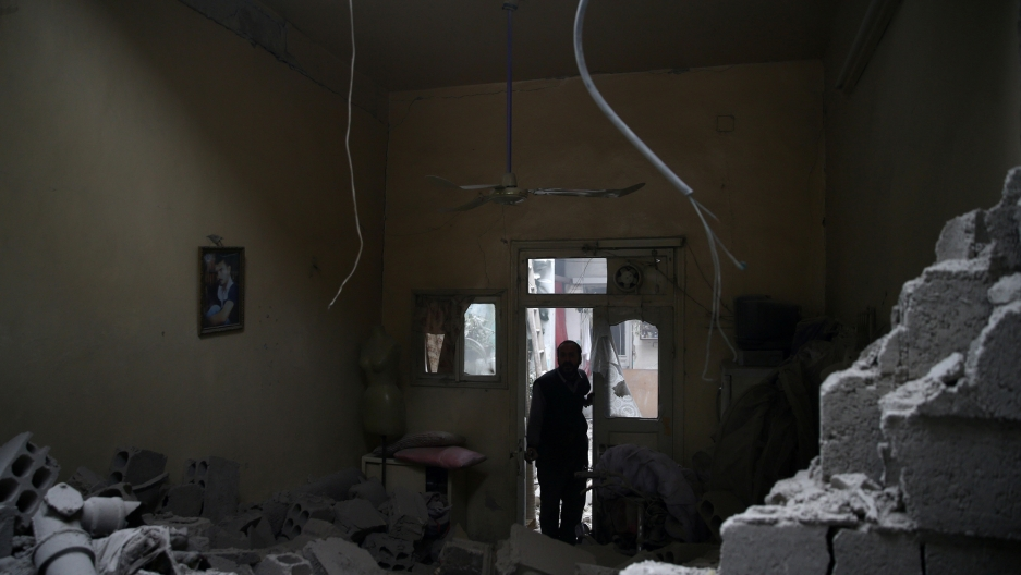 A man, center, stands in a back-light doorway looking into a room in rubble.