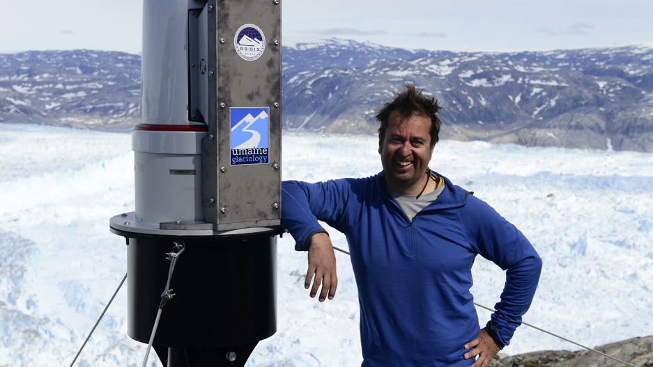 Gordon Hamilton with an automated laser scanning system installed to monitor Helheim Glacier, in Southeast Greenland. July 2015.