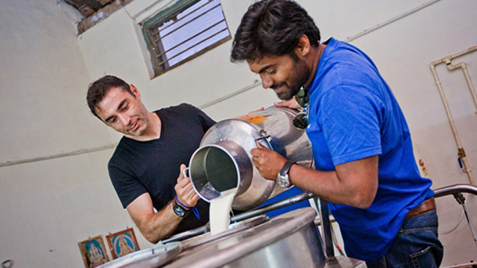 Sorin Grama, left, pours milk into his refrigeration system in India.
