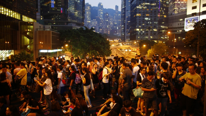 Protesters stand on a bridge as they block the main street to the financial Central district outside of the government headquarters building in Hong Kong on September 30, 2014.
