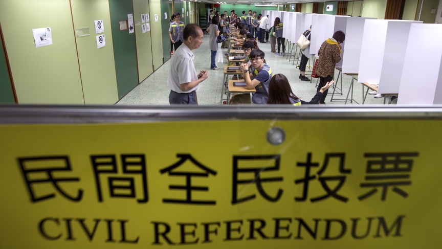 "Voters are guided inside a polling station during a civil referendum held by a group in Hong Kong called ""Occupy Central with Love and Peace."" The unofficial referendum sparked warnings from China's Communist Party leaders."