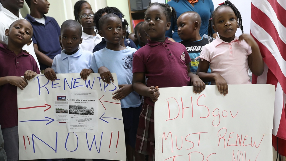 """A group of several young children stand in a line with placards reading """"Renew TPS Now."""""""