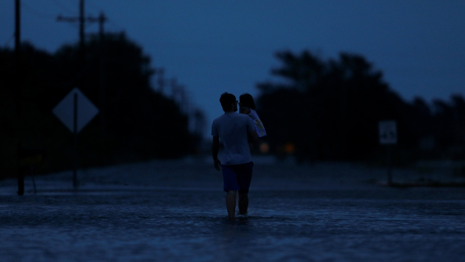 Ethan holds his 2-year-old daughter Zella as they walk through flood waters from Tropical Storm Harvey in Calcasieu Parish, Louisiana, on August 29, 2017.