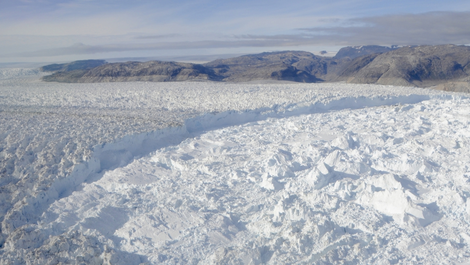 Dark rock above the Helheim glacier in southeastern Greenland marks its former level, before a sudden and dramatic retreat of hit many Greenland glaciers a decade ago. Scientists working on the Helheim and the fjord it drains into are looking for clues to