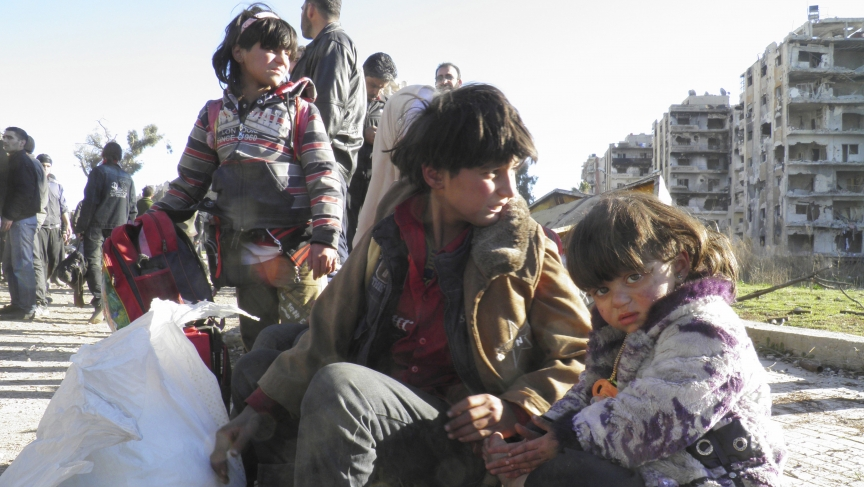 Children sit with their belongings as they wait to be evacuated from a besieged area of Homs February 12, 2014.