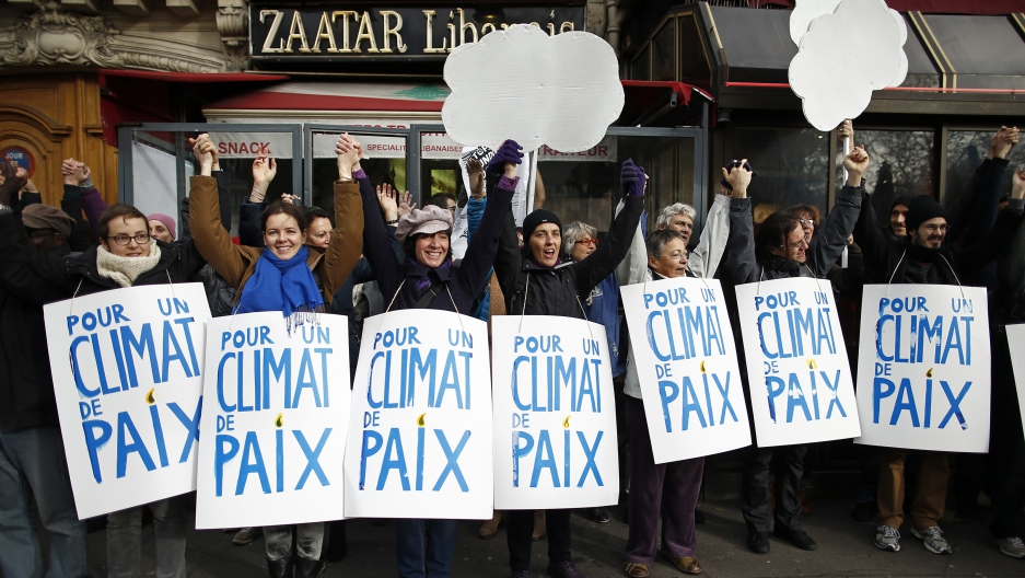 Climate activists formed a 2-mile human chain Sunday along Parisian sidewalks after authorities banned a full-fledged climate march following the Nov. 13 attacks in the French capital. Demonstrators said they were determined to find ways to express their