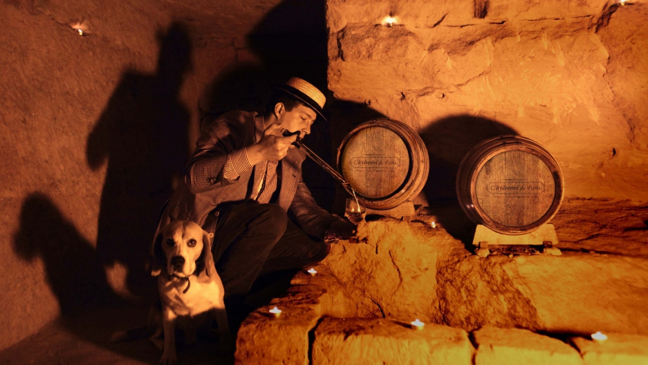Audric de Campeau pours a glass of mead in the Paris catacombs with his dog, Filou.