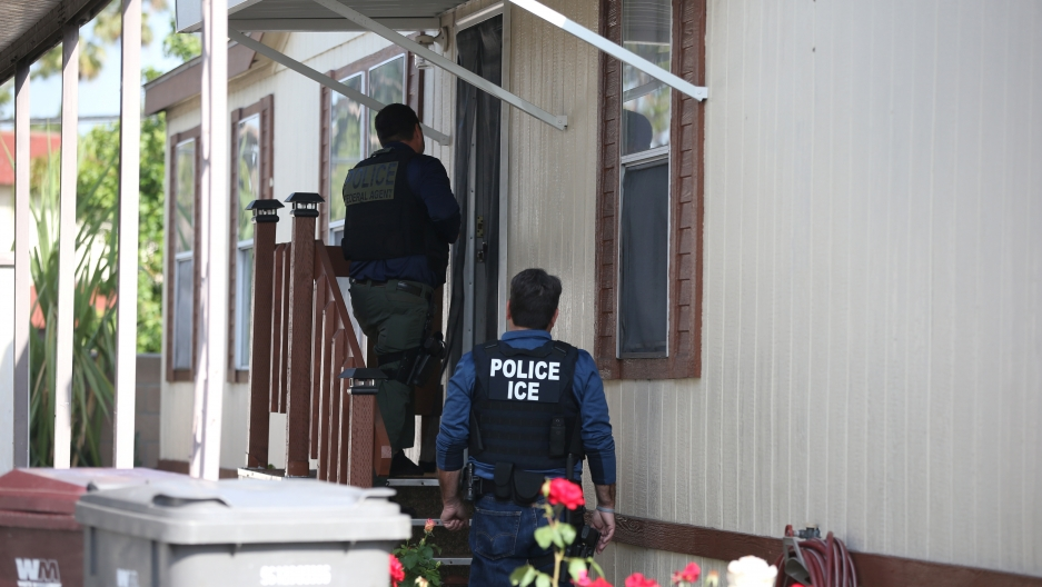 ICE agents knock on a door.