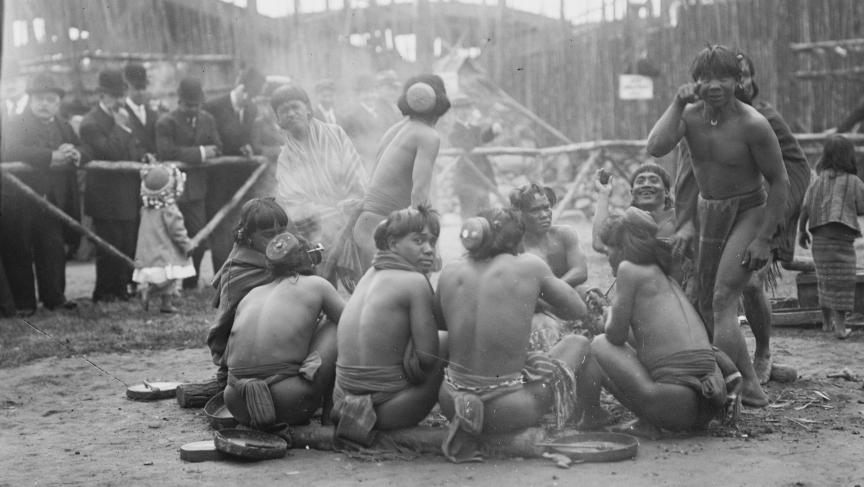 The Igorrotes sitting around a campfire, and playing up for the camera, at Coney Island in the summer of 1905.