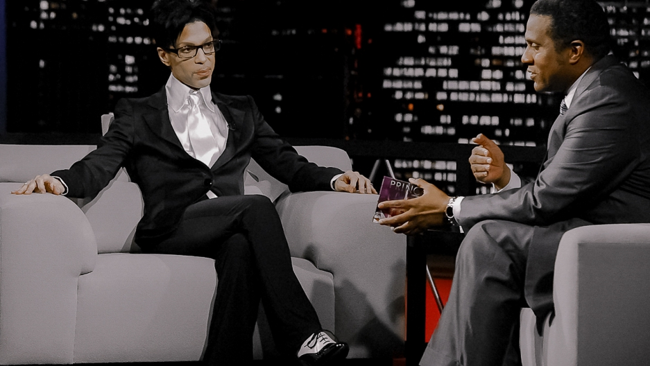 Prince, cross-legged on the set of the Tavis Smiley Show, looks at Smiley as he asks a question