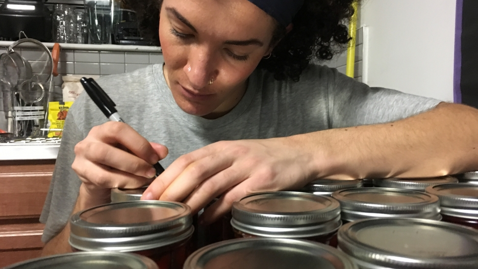 Woman in bandana leans over jars of green beans with permanent marker, writing on tops