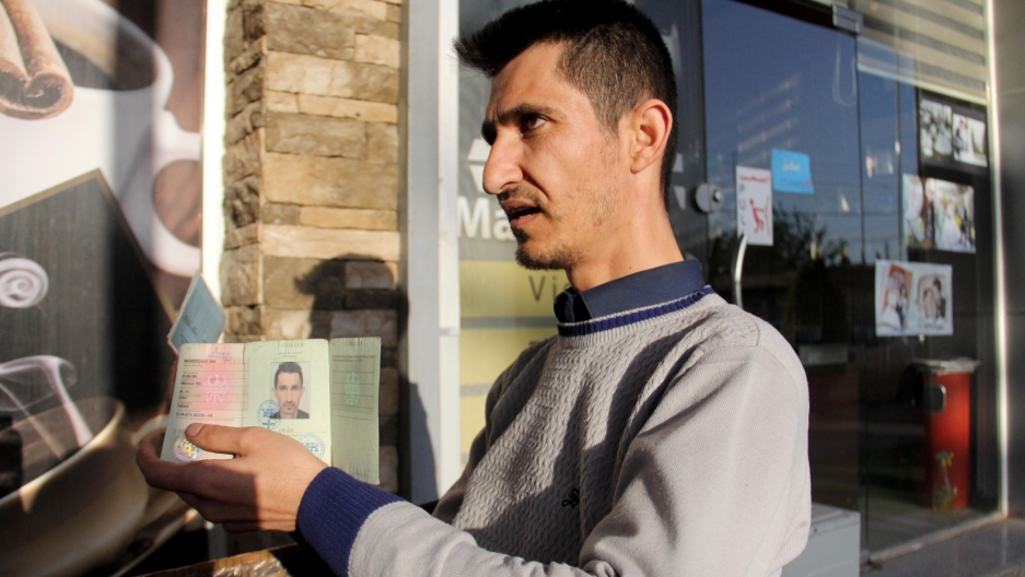 Dana Maghdeed Aziz holds up the identification issued to him by the Germany government.