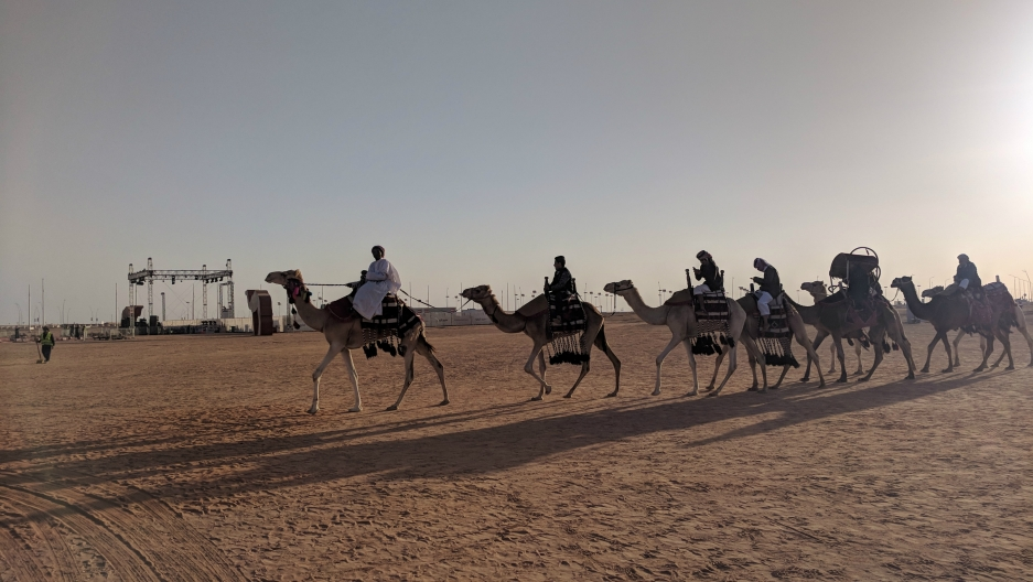"A man leads a caravan of camels at the King Abdulaziz Camel Festival in Saudi Arabia, a monthlong extravaganza honoring the ""ships of the desert"" and their place in the country's history."