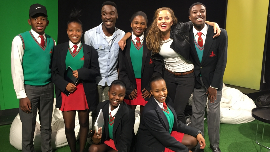 MTV Host Tinashe Venge, center, and Across Women's Lives reporter Jasmine Garsd, second from right, stand with South African students