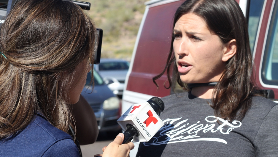 Gonzalez locked to a vehicle with a chain around her neck, being interview by a reporter.