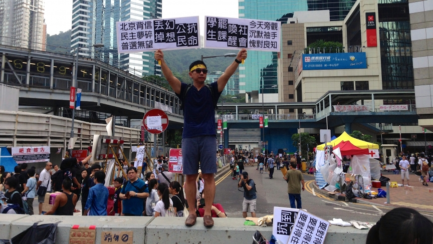 "A protester's signs urged Hong Kong citizens to ""wake up"" and join demonstrations, because ""Beijing is not trustworthy, and democracy is a broken dream""."