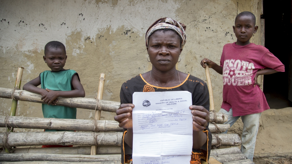 Ebola Survivor Gorma Dolo, holds an ebola free health certificate at her house in Freeman Reserve, Liberia.