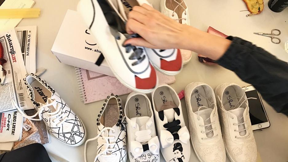 Maja Žirovčić rearranges the hand-painted shoes she's designed with co-founder, Ljudmila Mihajlović.