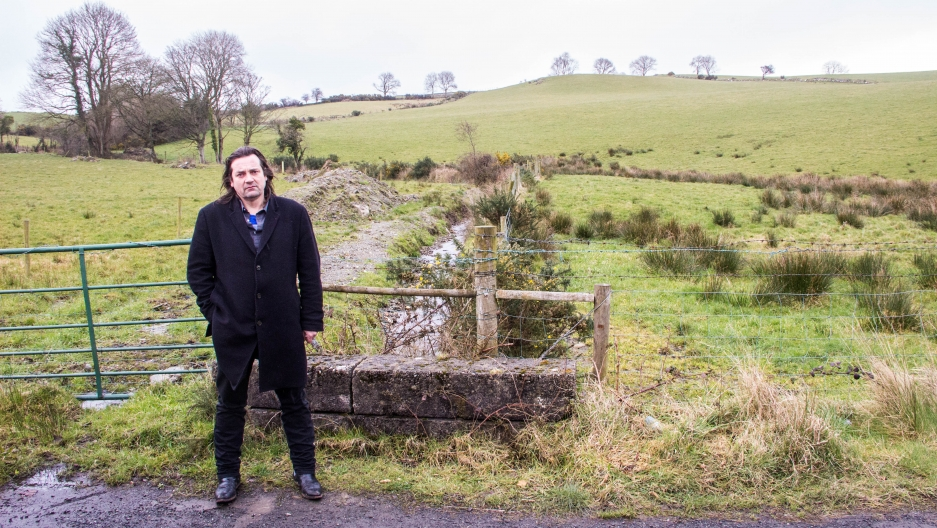 Éamonn Ó Ciardha teaches Irish language and history at Ulster University in Derry. The stream behind him marks the border between Northern Ireland and the Republic of Ireland. It's on a tiny country road just outside of Derry. Ó Ciardha says that trying t