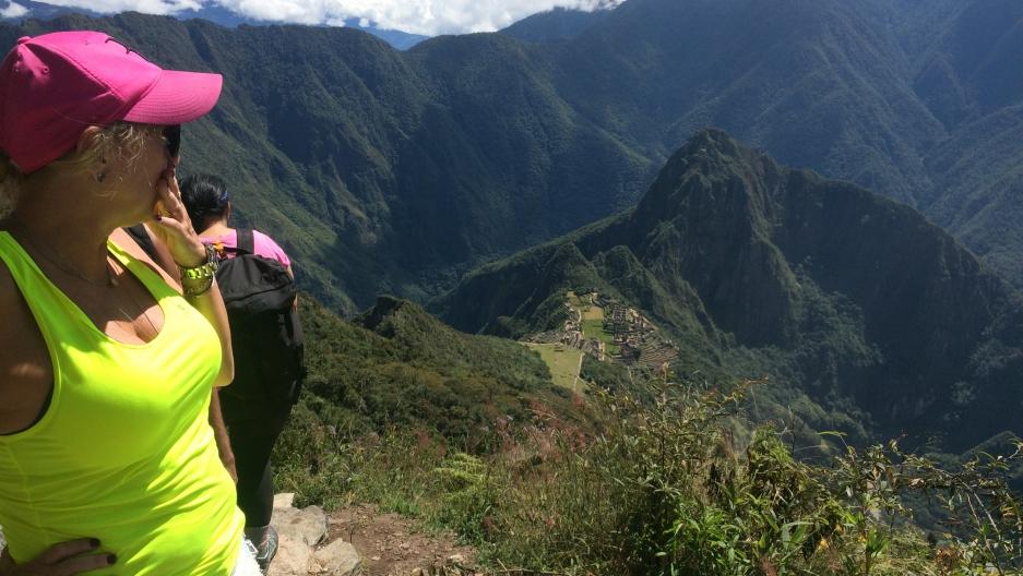 A tourist looks down at the Machu Picchu archeological site in Cuzco, Peru.
