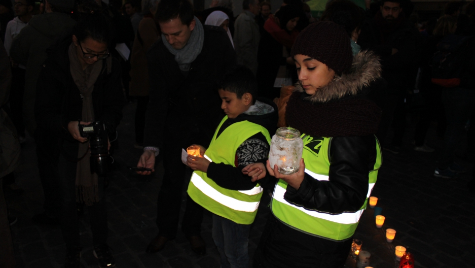 Children attend a candlelight vigil in the town square in Molenbeek, a neighborhood in Brussels with ties to the alleged perpetrators of the Paris attacks.