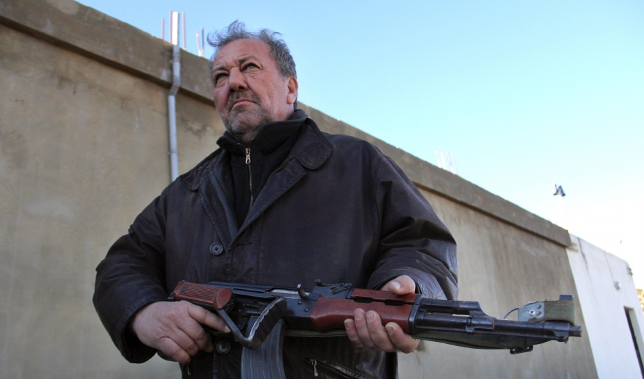 Ali Nasri Shamas holds a Kalashnikov assault rifle outside his hashish factory in Lebanon's Bekaa Valley. Shamas says the region's hash growers are ready to turn their weapons against any Islamic militants crossing the border from Syria.