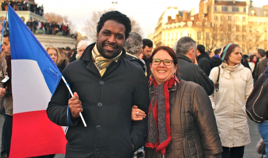 Paris couple Ahmed and Florence march hold the flag of France while participating in a march in support of freedom and people slain in the Charlie Hebdo terrorism attacks on January 12, 2015.