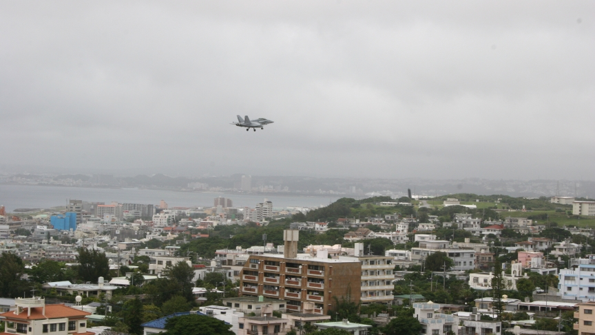 A US military aircraft prepares to land on a runway at the Futenma military base, adjacent to a densely populated city on Okinawa island.