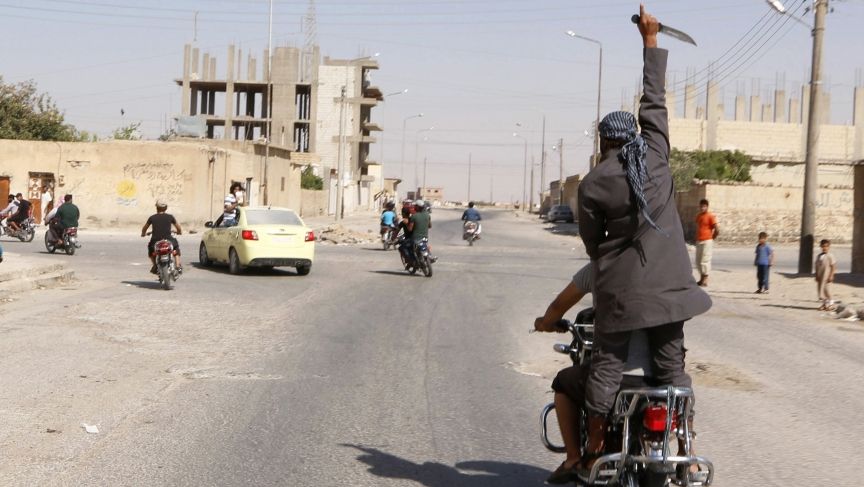A man holds up a knife as he rides on the back of a motorcycle touring the streets of Tabqa in celebration after ISIS militants took over Tabqa air base in Syria, on August 24, 2014.