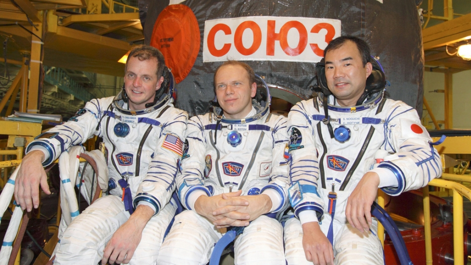 At the Baikonur Cosmodrome in Kazakhstan, ISS Expedition 22 crew members take a moment for photographs following a fit check of their Soyuz TMA-17 spacecraft at the launch site's integration facility in December 2009.