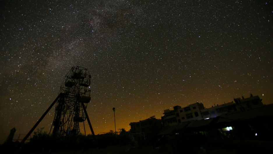 A ferris wheel stands in the rebel-controlled area of Maaret al-Numan town in Idlib province, Syria. Stars fill the night sky over the Syrian rebel-held city of Idlib, and the streets are eerily quiet.