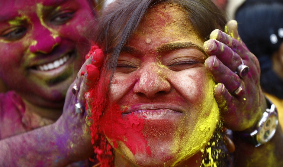A student of Rabindra Bharati University reacts as her fellow student applies colored powder on her face during celebrations for Holi in Kolkata.