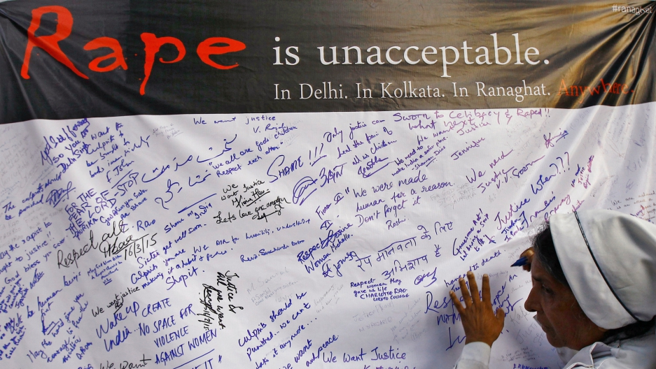 A Catholic nun signs a banner during a rally to show solidarity with a nun who was raped during an armed assault on a convent school, in Kolkata.