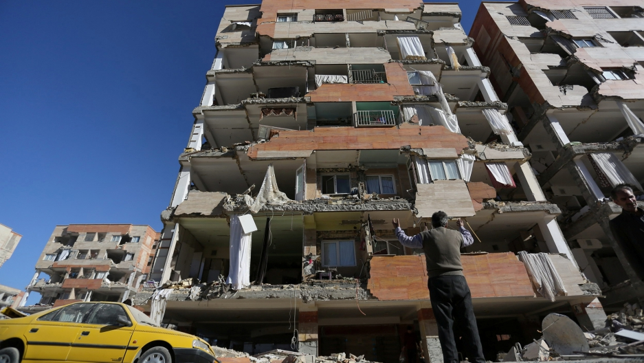 A man stands on the street with this arms raised looking up at a building with most of the walls broken off.