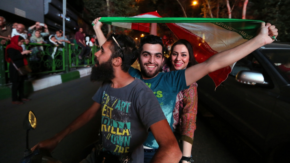 Iranians wave the national flag during celebrations in  Tehran on July 14, 2015, after Iran's nuclear negotiating team struck a deal with world powers in Vienna.