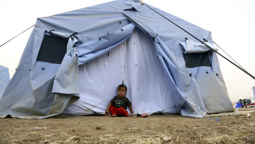 A boy who fled from the violence in Mosul sits outside a tent at a camp on the outskirts of Erbil in Iraq's Kurdistan region.