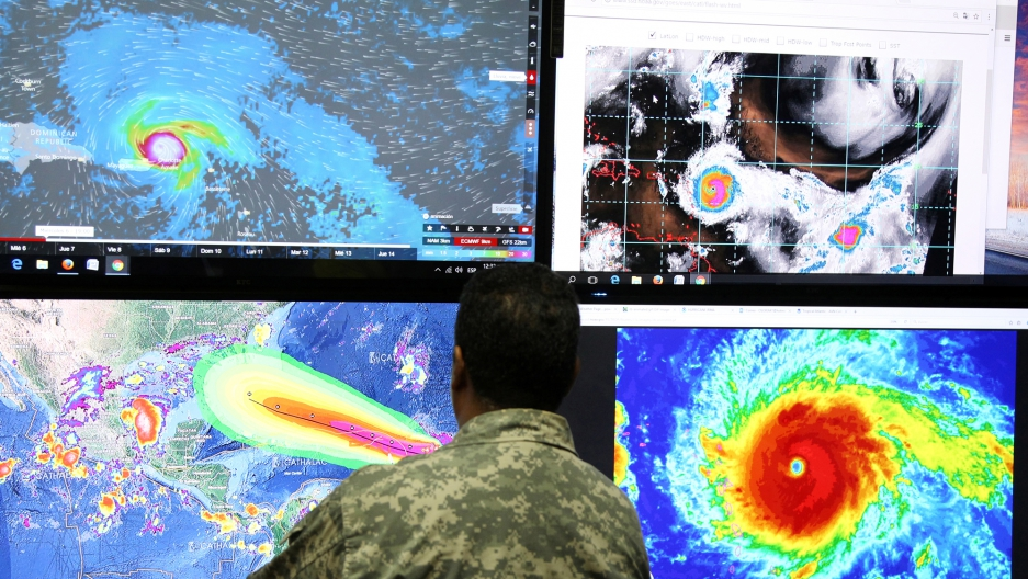 A member of the Emergency Operations Committee standing in front of four TV monitors with images of Hurricane Irma shown.