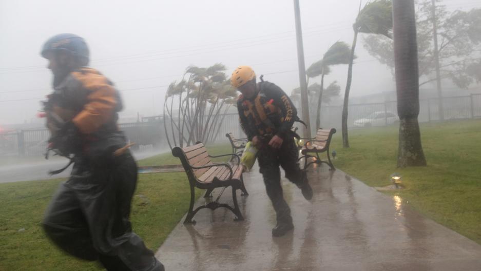 Members of the civil defense run as Hurricane Irma howls past Puerto Rico after thrashing several smaller Caribbean islands.