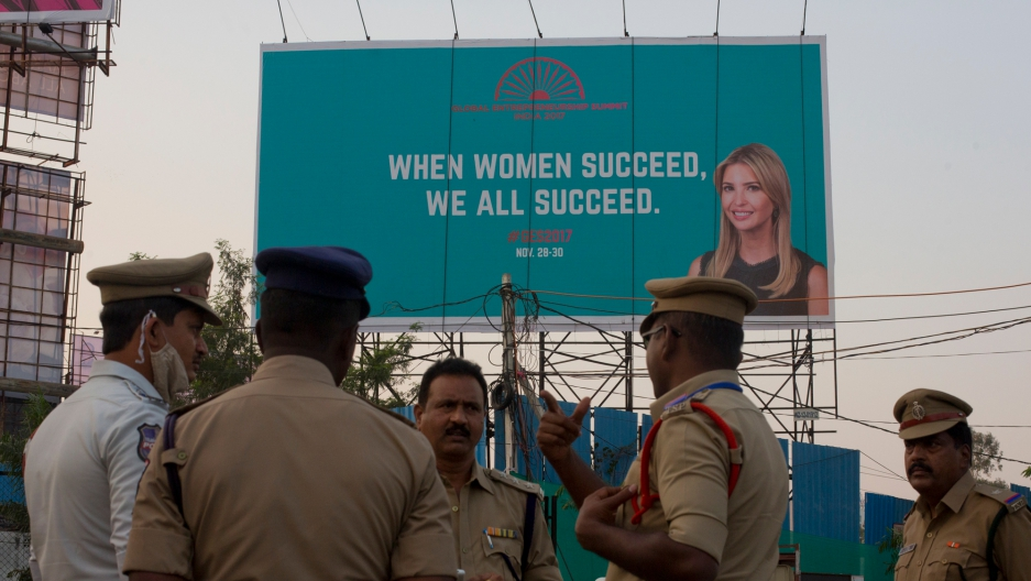 Five uniformed Indian security officials speak to each other with a billboard featuring Ivanka Trump in the background.