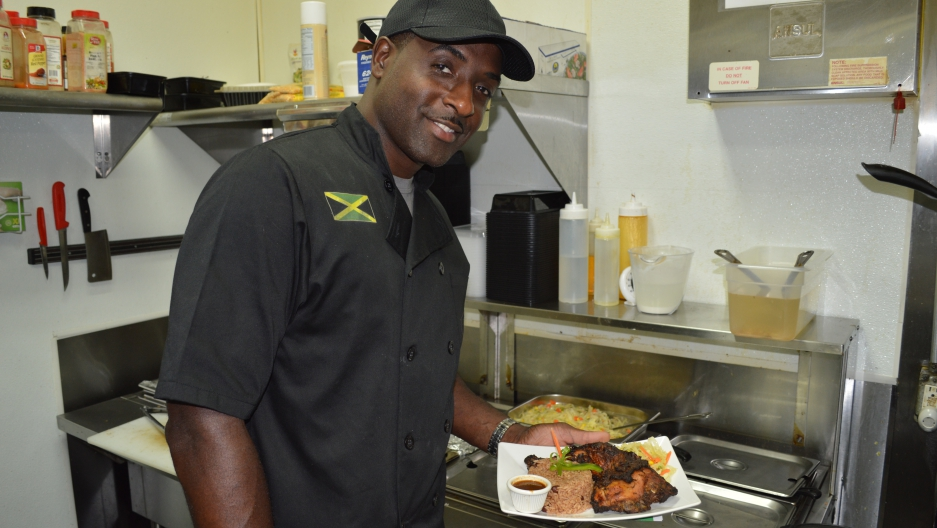 Chef in kitchen presents grilled chicken